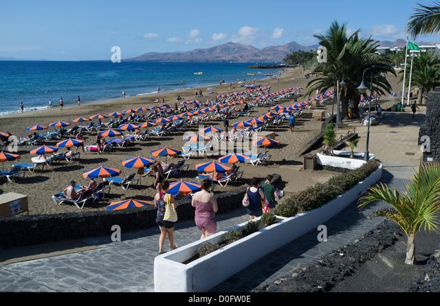 Lanzarote beach sunloungers stock photos lanzarote beach - Lanzarote walks from puerto del carmen ...