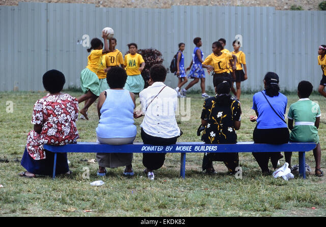 School children and parents watching a girls netball match at Churchill Park. Lautoka. Fiji. South Pacific. - Stock Image