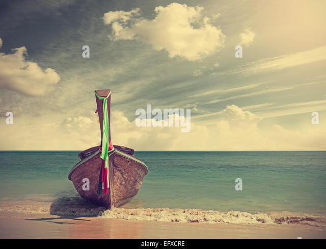 Retro filtered picture of a wooden boat on beach. - Stock Image