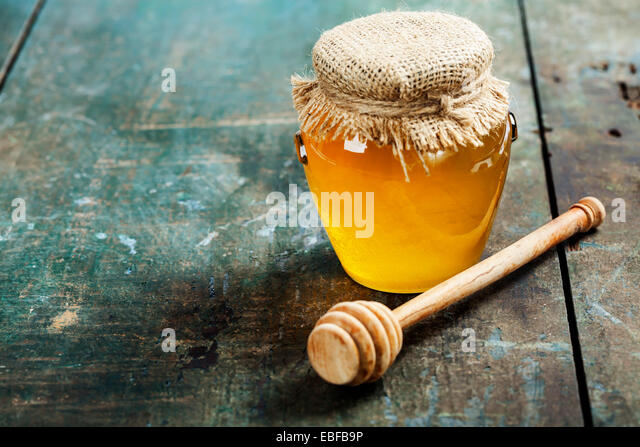 Honey jar and dipper on wooden background - Stock Image