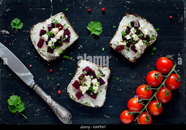 Goat cheese, roasted beet and feta cheese appetizer sandwiches on black cutting board, top view - Stock Image