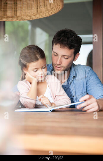 Father and young daughter reading together - Stock Image