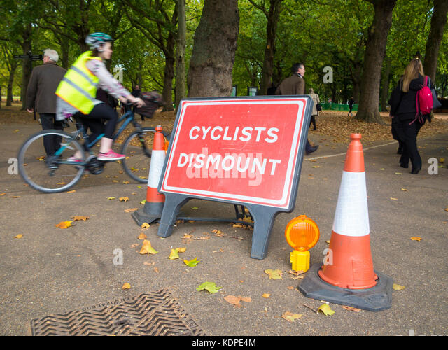 Cyclists ignore the sign that instructs them to dismount from their bicycles - Stock Image
