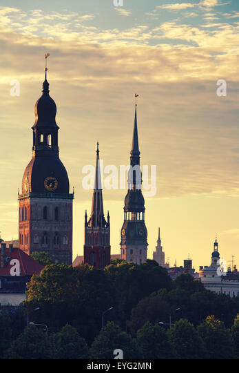 Latvia. Early summer morning on the spire of the cathedral with the cocks for the trees in Riga - Stock Image