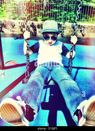 A young boy wearing hat and sunglasses plays on s swing in the park. - Stock-Bilder