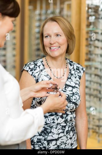 Salesgirl Assisting Senior Customer In Selecting Glasses - Stock Image