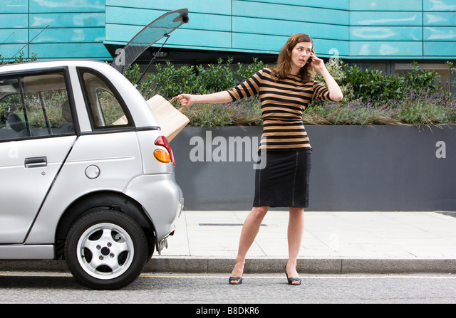 Woman on cellphone by car - Stock Image