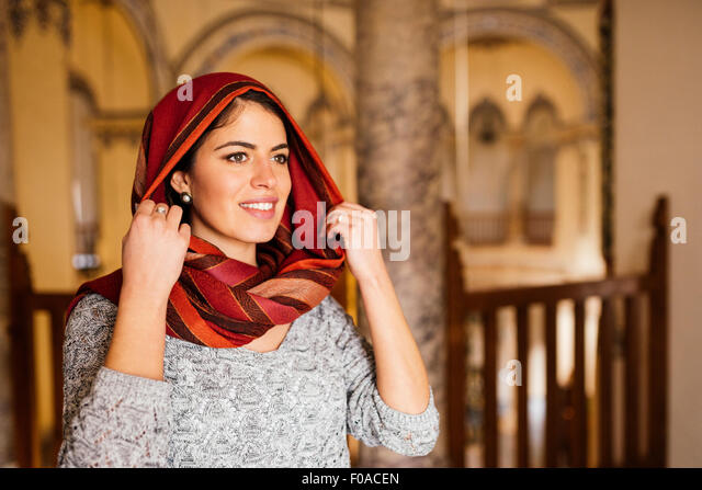 Young woman in mosque, wearing headscarf, Istanbul, Turkey - Stock Image