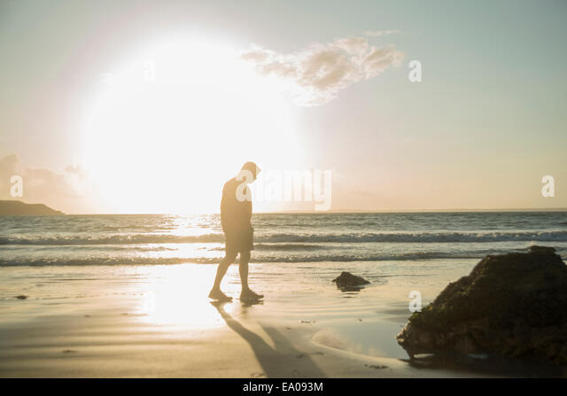 Mature man, walking on beach, along coastline - Stock Image