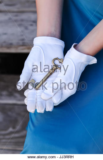 Skeleton key in a woman's gloved hand - Stock Image