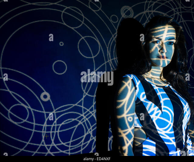 Digital Art: a young woman girl with a swirling spiral digital image pattern projected onto her face. - Stock Image