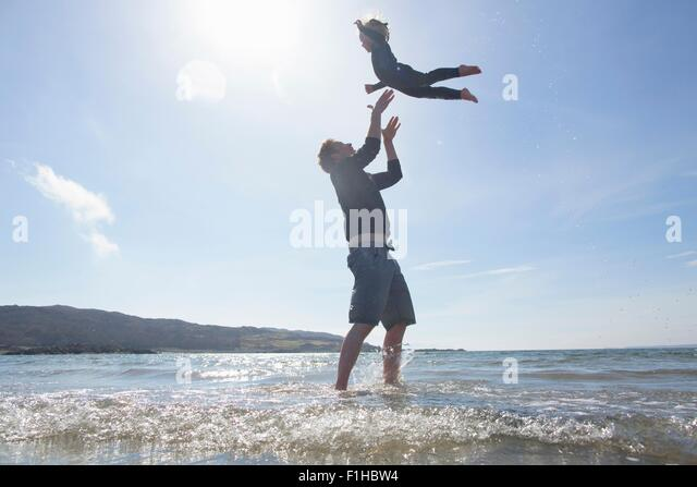 Father throwing son in air on beach, Loch Eishort, Isle of Skye, Hebrides, Scotland - Stock Image