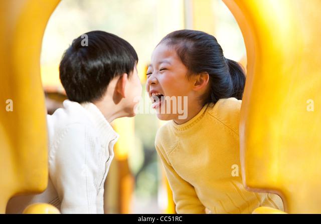 Children playing on playground slide - Stock Image