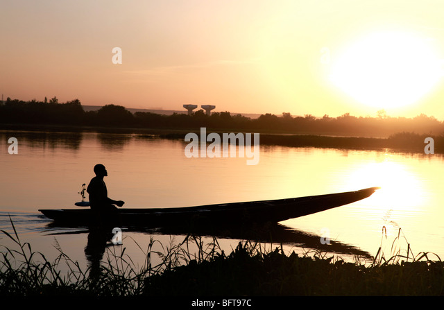 Fisherman in a small boot crossing a river at sunset - Stock-Bilder