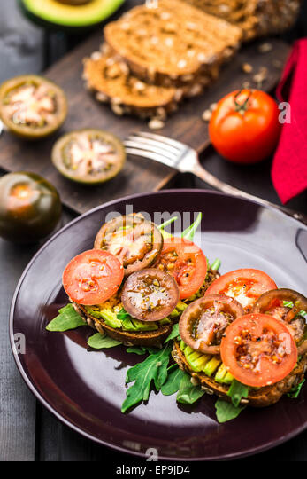Avocado sandwich with arugula and tomatoes on a plate - Stock Image