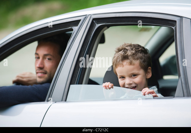Father and son smiling out car window at camera - Stock Image