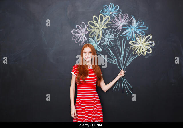 Smiling attractive redhead young woman standing and holding bouquet of drawn flowers over blackboard background - Stock-Bilder