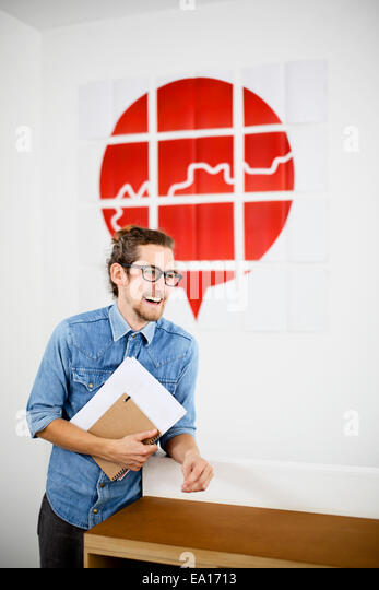 Young man in design office, smiling - Stock Image