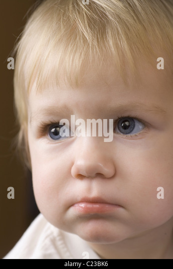 Blonde 14 month old with downcast expression - Stock Image