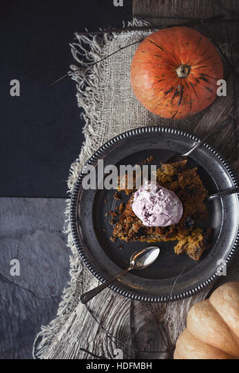 Pumpkin dump cake with ice cream on the metal plate on the stone table  vertical - Stock Image