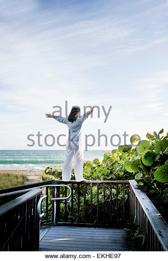Mature woman with arms open on top of walkway railing, Juno Beach, Florida, USA - Stock Image
