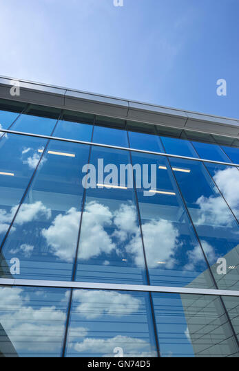 PUFFY WHITE CLOUDS BLUE SKY REFLECTED ON GLASS OFFICE BUILDING WINDOWS - Stock-Bilder