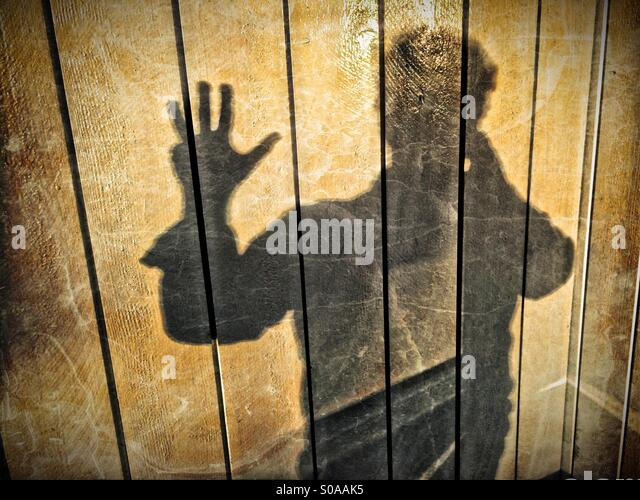 A man casting a shadow on a wall, counting on his hand. Number four. - Stock Image