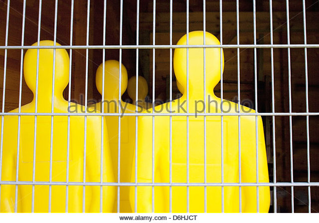 Yellow Football dummies behind wire fence Munich Germany - Stock Image