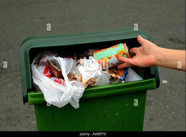 Person putting aluminum can into overflowing trash bin - Stock Image