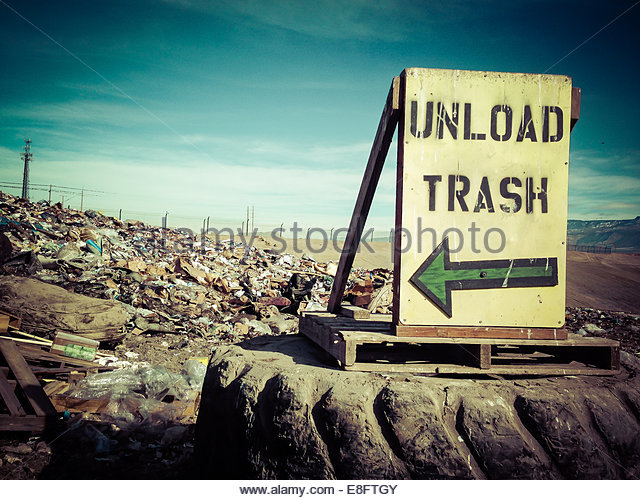 Unload Trash' sign on landfill - Stock Image