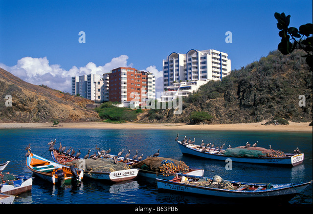 Venezuela fishing boats pelicans skyline from La Caracola cove Isla Margarita island Porlamar City space south america - Stock Image