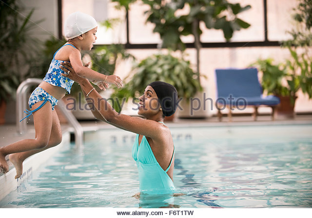 Mother and daughter playing in swimming pool - Stock-Bilder