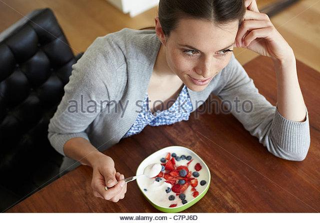 Woman eating yogurt and fruit - Stock Image