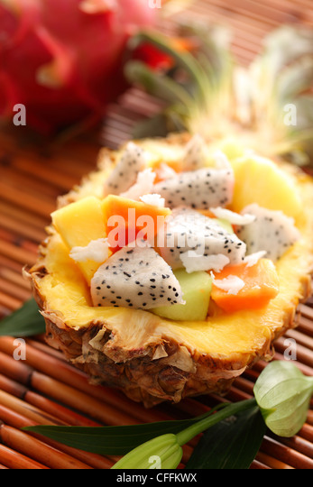 Tropical salad with dragon fruit and papaya inside pineapple - Stock Image