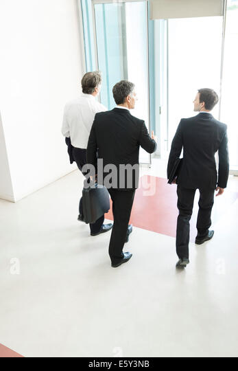 Business associates leaving office building together - Stock-Bilder