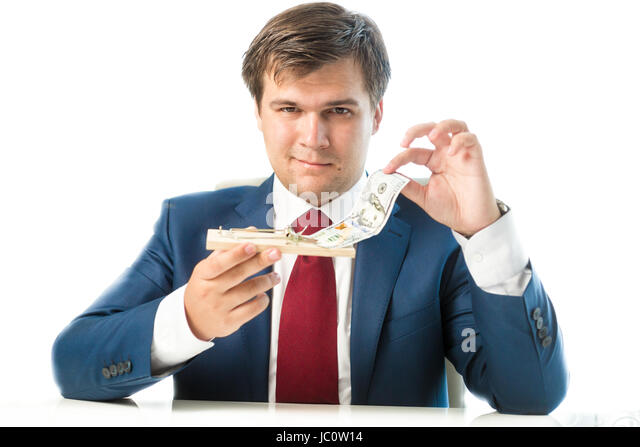Portrait of cunning businessman taking dollar bill out of mousetrap - Stock Image