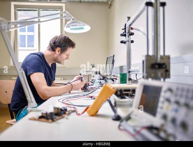 Man soldering in electronics laboratory - Stock Image