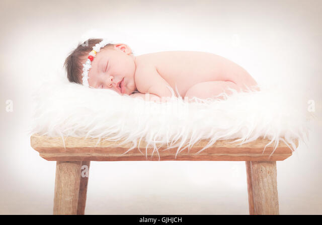 Portrait of a newborn baby girl sleeping on fluffy rug - Stock Image