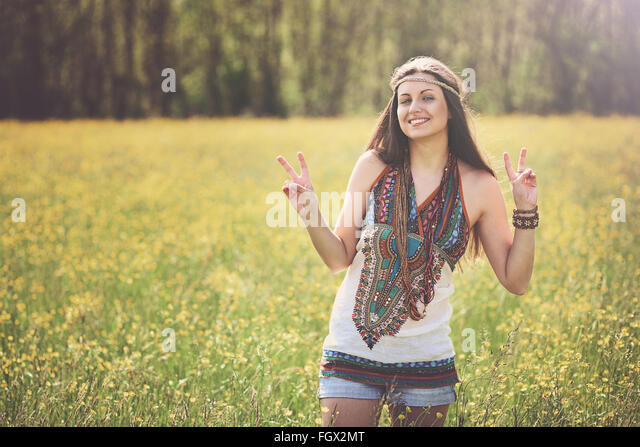 Peace sign from smiling hippie in a meadow. Freedom and harmony - Stock Image