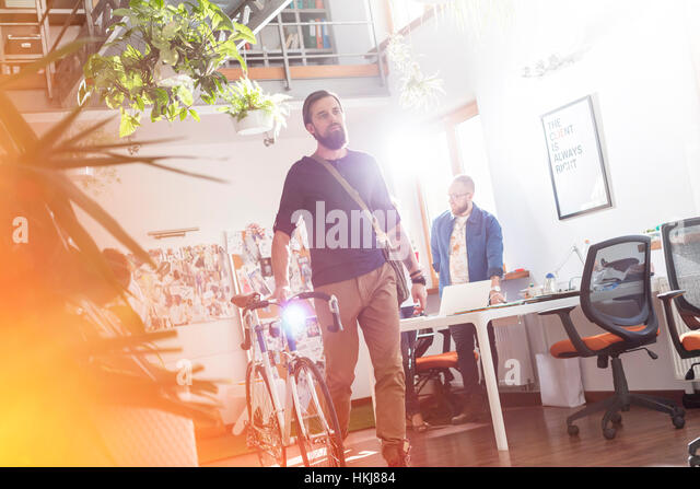 Male design professional walking bicycle through office - Stock-Bilder