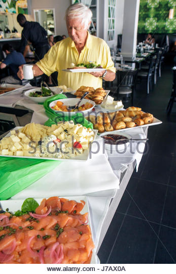 Miami Beach Florida Eden Restaurant brunch buffet table pastry fruit food smoked salmon man senior choices - Stock Image