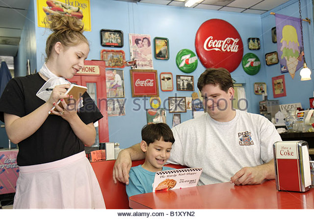 Arkansas Ozark Mountains Hardy Main Street Hardy Malt Shoppe man boy father son child girl teen waitress read menu - Stock Image