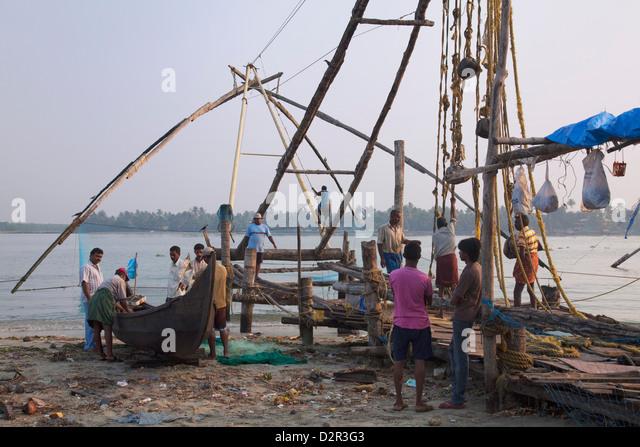 Fishermen preparing traditional boat and Chinese fishing net on the waterfront at Kochi (Cochin), Kerala, India, - Stock Image