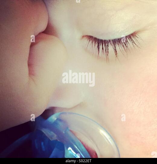 Close-up of a baby boy sleeping with a blue dummy soother in his mouth. - Stock Image