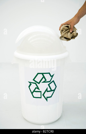 Man's hand placing cardboard in recycling bin, cropped - Stock Image