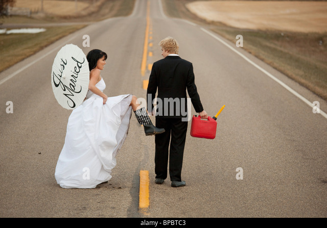 three hills, alberta, canada; a bride and groom walk down a rural road with a jerry can and a parasol saying 'just - Stock Image