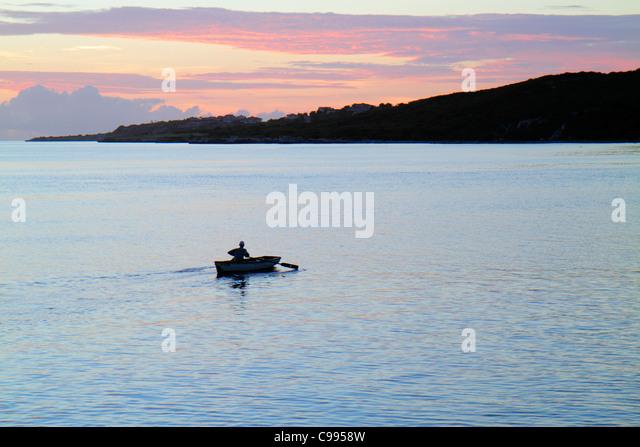 Curaçao Netherlands Antilles Dutch Piscadera Bay Caribbean Sea rowboat man twilight calm ocean clouds coastline - Stock Image