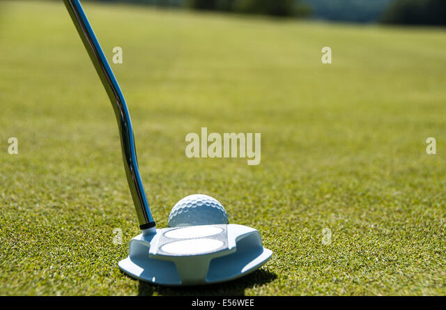 Golfer about to putt a white golf ball on the green towards a black and white checkered flag - Stock Image