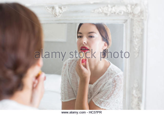 Mid adult woman applying make-up in mirror. - Stock Image