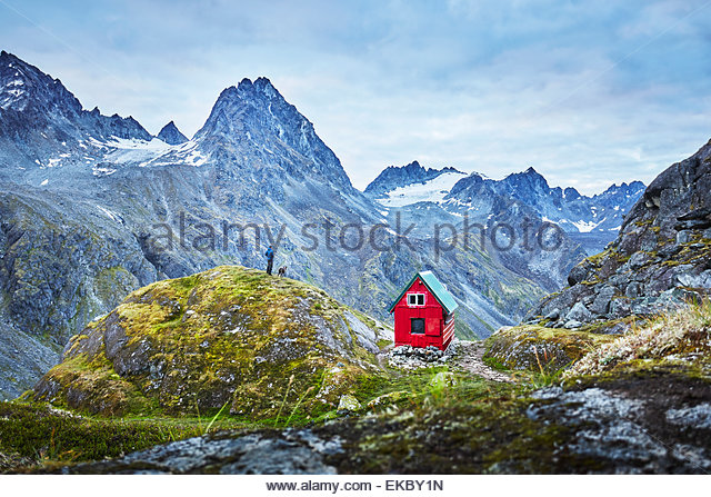 Distant view of male hiker and dog on top of mountain, Palmer, Alaska, USA - Stock Image